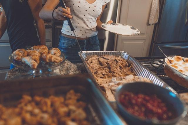 žena a muž naberajú jedlo pri stoloch s občerstvením