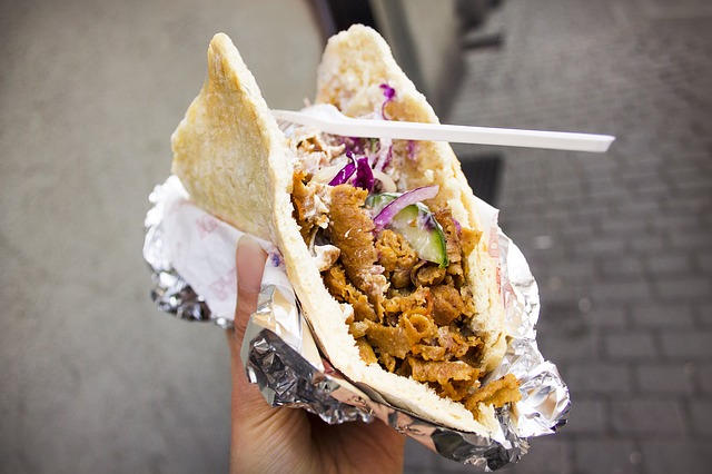 človek drží v ruke kebab zabalený do alobalu