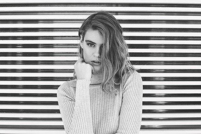 Sexy žena v svetri stojí pri okne so žalúziami a drží sa za tvár.jpg
