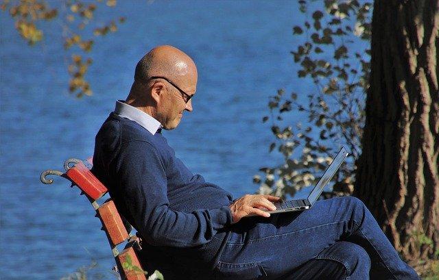 Muž bez vlasov sedí na lavičke v parku a pozerá do notebooku.jpg