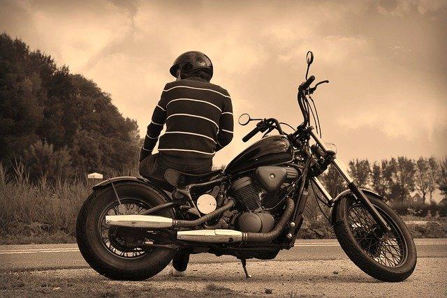 Chlap v prilbe sedí na odparkovanej motorke