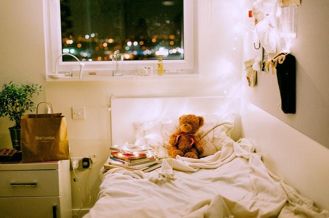 Posteľ v detskej izbe s plyšovými medveďmi a svetielkami