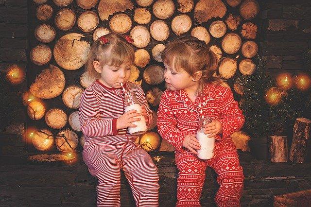 Dve dievčatá v červených pyžamách pijú mlieko