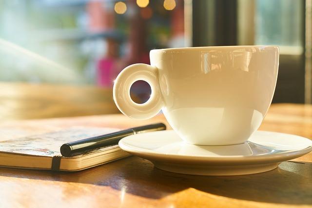 Zápisník pero  a šálka kávy položené na stole